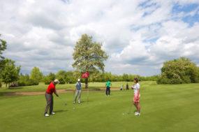 Golferinnen und Golfer spielen auf den Übungsanlagen.