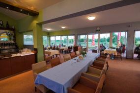 Bild mit gedeckter Tafel, Stühlen und Weinbar im Innenbereich des Golfclub-Restaurants.