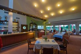 Innenbereich des Golfclub-Restaurants mit gedeckten Tischen und Stühlen.