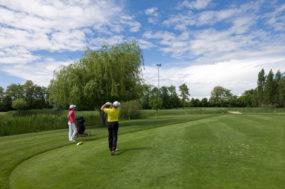 Zwei Menschen spielen Golf bei sonnigem Wetter, wobei einer gerade abgeschlagen hat.