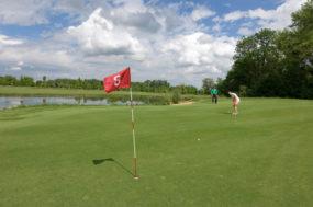 Bild mit Golfspieler nach seinem Putt, wobei der Ball das Ziel noch nicht erreicht hat.