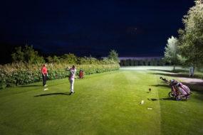Ein Mann und eine Frau golfen bei Nacht, wobei die Frau gerade abgeschlagen hat.