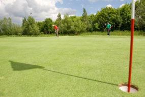 Bild eines Golflochs mit Fahne, im Hintergrund befindet sich ein Mann kurz vor dem Abschlag.