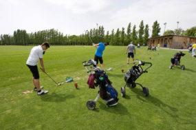 Drei Menschen trainieren mit ihren Ausrüstungen auf der Übungsanlage des Golfplatzes, wobei der erste gerade abgeschlagen hat und der Zweite sich auf den Abschlag vorbereitet.
