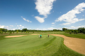 Zwei Menschen spielen auf der Golfanlage, wobei sich einer gerade auf den Abschlag vorbereitet.